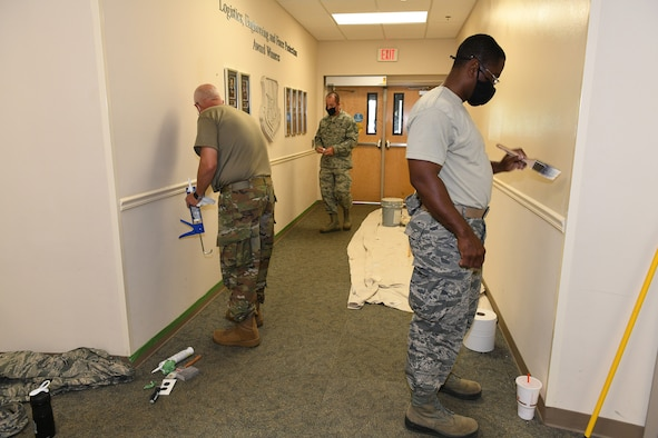 Photo shows three Airmen painting walls in a hallway.