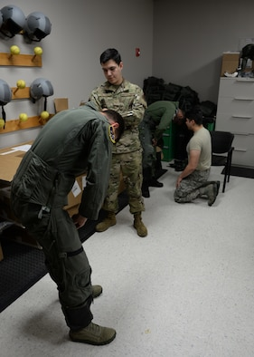 Two 37th Flying Training Squadron student pilots try on G-suits, while two 37th FTS Aircrew Flight Equipment specialists make sure the suit fits correctly on June 10, 2020, at Columbus Air Force Base Miss. A G-suit helps pilots withstand the acceleration forces put on their bodies while maneuvering aircraft. (U.S. Air Force photo by Airman 1st Class Davis Donaldson)