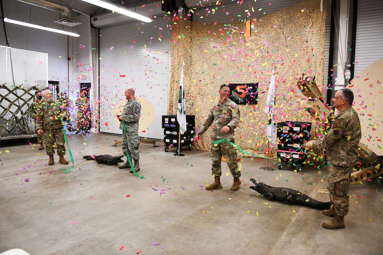 Photo shows Airmen cutting a ribbon with confetti falling from above.