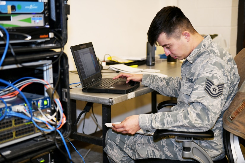 Photo shows an Airman working on a laptop next to a stack of boxes with wires coming out.