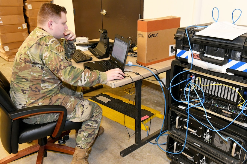 Photo shows an Airman working on a laptop connected to a tower of communications equipment.