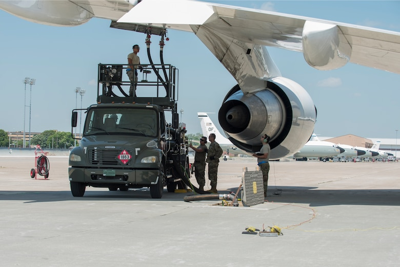 A team looks on as an aircraft is refueled.