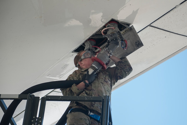 an Airman connects a large hose to an aircraft.