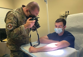 Photo shows a picture of an Airman taking the picture of a patient's arm.