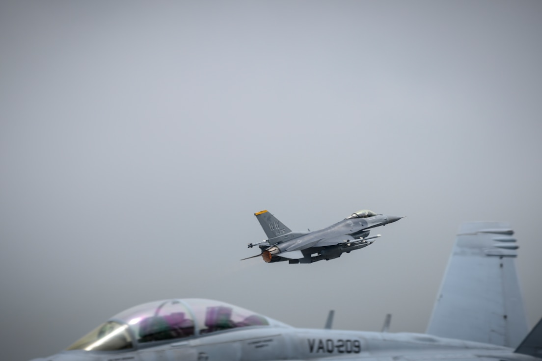 A U.S. Air Force F-16 Fighting Falcon flies over a U.S. Navy Boeing EA-18G during a PAC Weasel exercise at Misawa Air Base, Japan, June 19, 2020. This exercise allows 35th Operations Group intelligence Airmen, and the U.S. Navy Electronic Attack Squadron 209 (VAQ-209) to integrate at a classified level. This coordination and sharing of training and operational tactics techniques and procedures (TTPs) is extremely helpful. (U.S. Air Force photo by Airman 1st Class China M. Shock)
