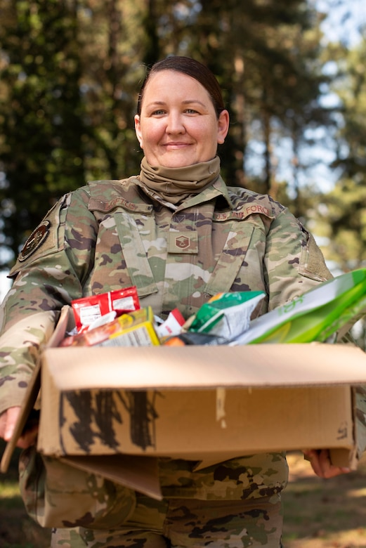 Master Sgt. Aisling Loftus, 100th Force Support Squadron postal superintendent, with a care package she assembled at RAF Mildenhall, England, June 15, 2020. Team Mildenhall has donated approximately 3,000 items to support the wellness of local healthcare workers fighting COVID-19. (U.S. Air Force photo by Airman 1st Class Joseph Barron)