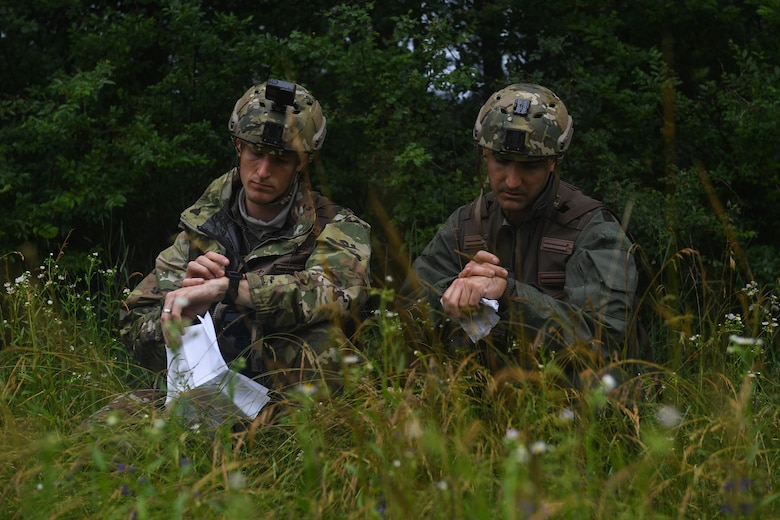 U.S. Air Force Capt. James Gregory, 510th Fighter Squadron pilot and Maj. Matthew Robins, 555th Fighter Squadron pilot, use their radios during an exercise at Rivolto Air Base, Italy, June 10, 2020. The pilots were undergoing a simulated Survival, Evasion, Resistance, Escape (SERE) training in which they had to survive and make contact with the proper sources after landing in enemy territory. (U.S. Air Force photo by Airman 1st Class Thomas S. Keisler IV)