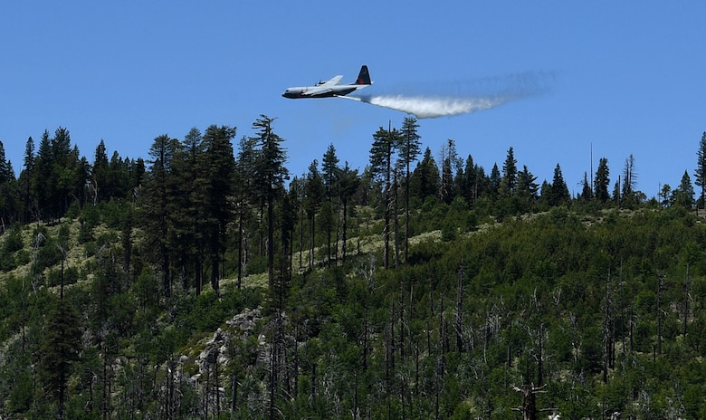 About 150 feet above a tree line, a California Air National Guard C-130 aircraft releases 3,000 gallons of water, covering nearly a quarter mile, during aerial wildland firefighting training June 15-19, 2020, at the Tahoe National Forest.