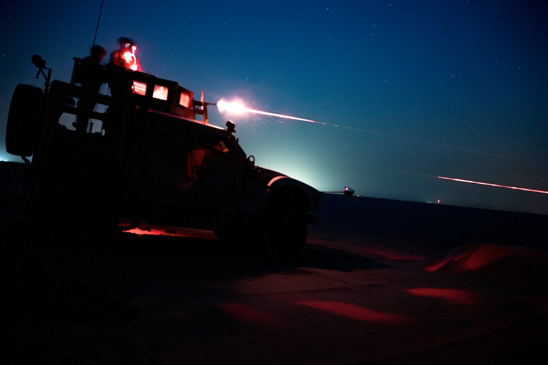 U.S. Marines fire an M240B from an MRAP All-Terrain Vehicle on a night time machine gun range in Kuwait, June 16.