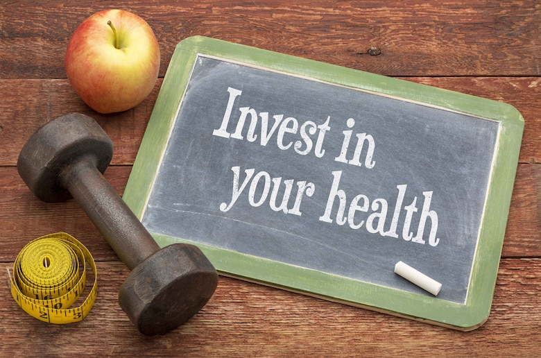 """Graphic says """"Invest in your health"""" written on a small chalkboard and has a dumb bell, measuring tape and apple next to it."""
