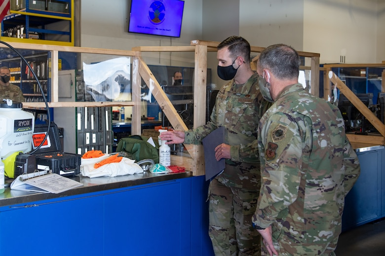 Tech. Sgt. Nathan Nachatilo, 62nd Aircraft Maintenance Squadron, left, explains the process of aircraft decontamination to Gen. David Goldfein, chief of staff of the Air Force, right, at Joint Base Lewis-McChord, Wash., June 18, 2020. During his tour of Team McChord, Goldfein visited the Western Air Defense Sector, 62nd Maintenance Squadron, 62nd Aircraft Maintenance Squadron and the 7th and 4th Airlift Squadrons to see how their mission shave been impacted by COVID-19. (U.S. Air Force photo by Senior Airman Sara Hoerichs)