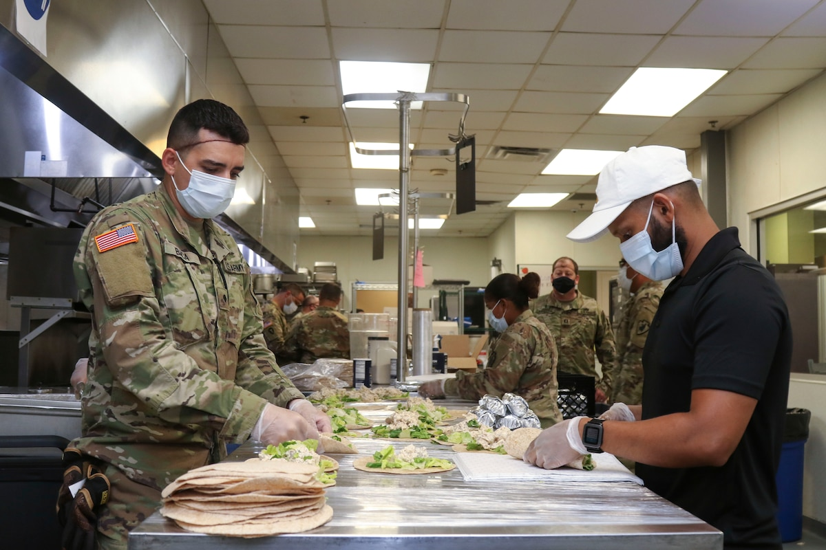 Soldiers wearing protective gear prepare meals in a kitchen.
