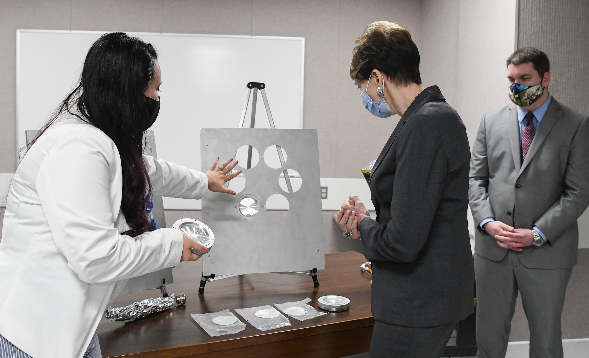 Kellye Burns, left, a space test engineer, shows Secretary of the Air Force Barbara Barrett some of the hardware and samples used during a materials test in teh Space Threat Assessment Testbed at Arnold Air Force Base, Tenn., June 18, 2020. Also pictured is John Claybrook, capability manager for Space Asset Resilience. (U.S. Air Force photo by Jill Pickett)