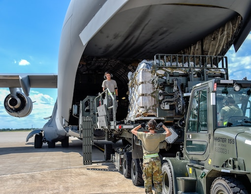 Air transportation specialists direct and load medical supplies onto a C-17 Globemaster III