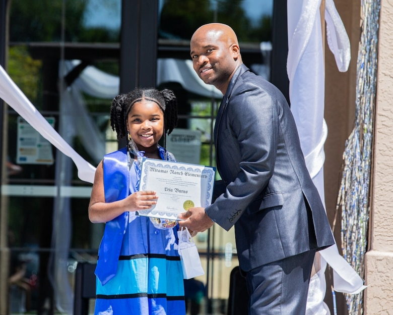 Leia Burns, an elementary graduate from Miramar Ranch Elementary, receives her certificate from Isiah Burns, her father, at the Milcon Clubhouse on Marine Corps Air Station Miramar, California, June 13, 2020.