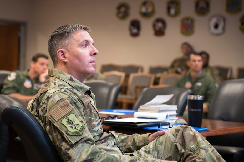 A photo of a Colonel listening to a briefing.
