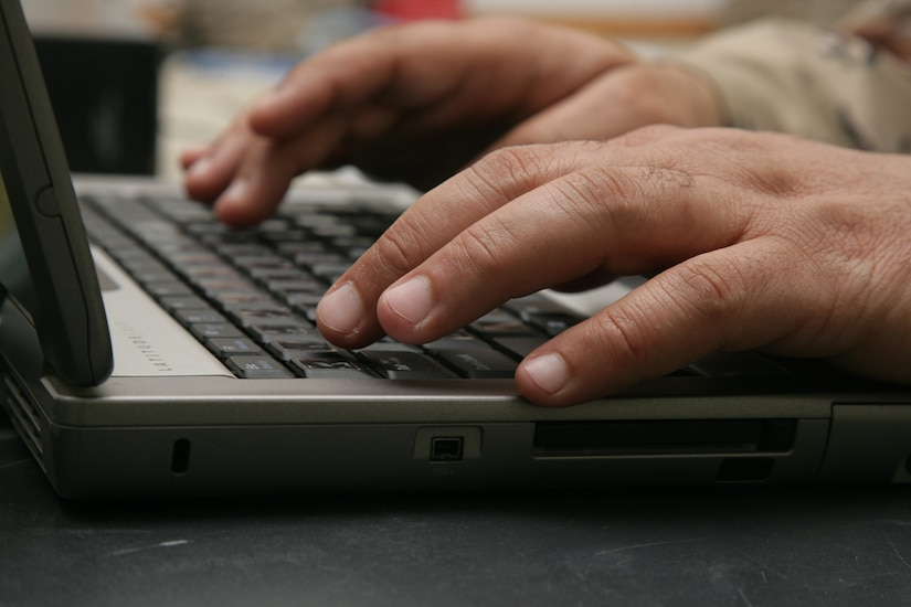 A service member types at a laptop keyboard.