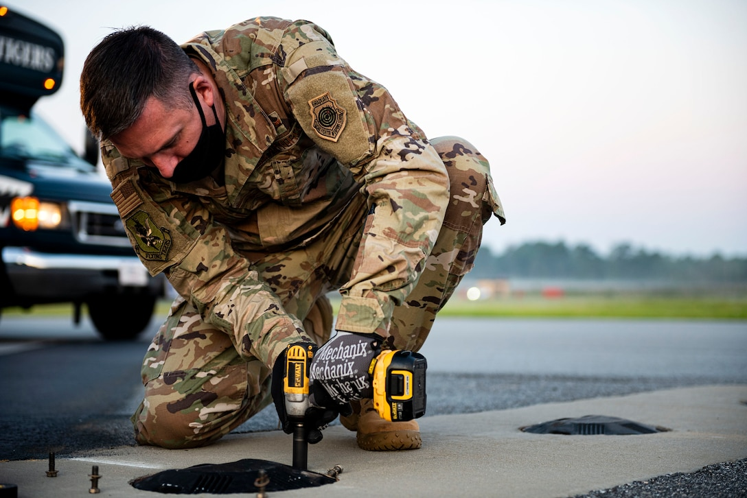 Photo of commander replacing an airfield light.