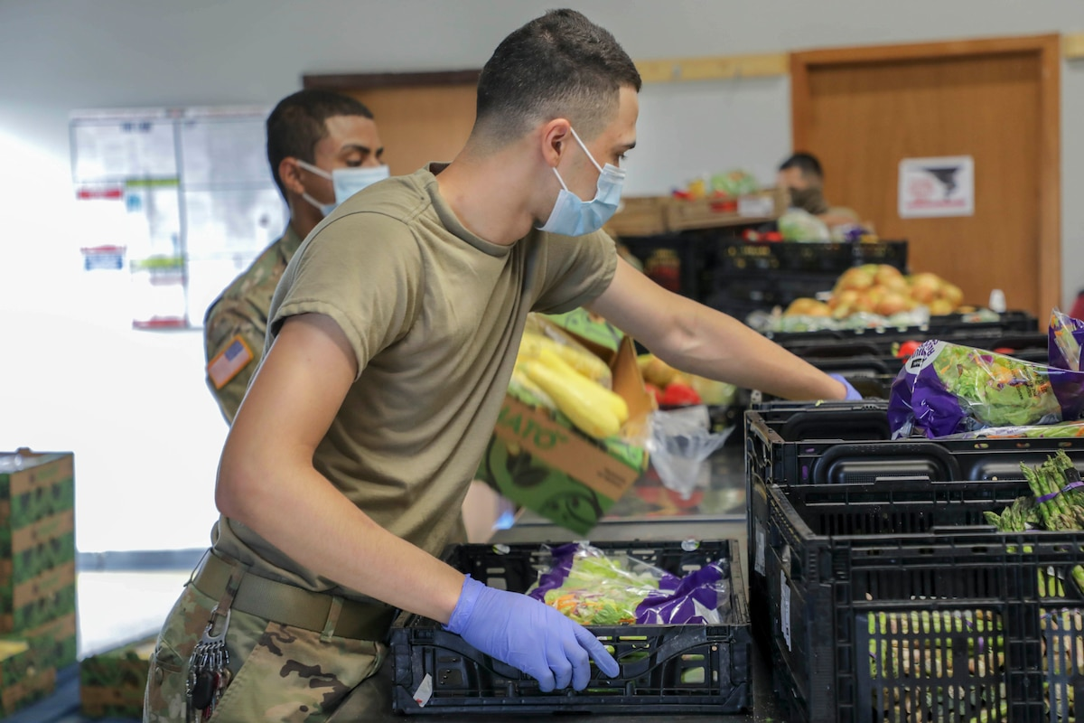 A soldier packs food into a crate.
