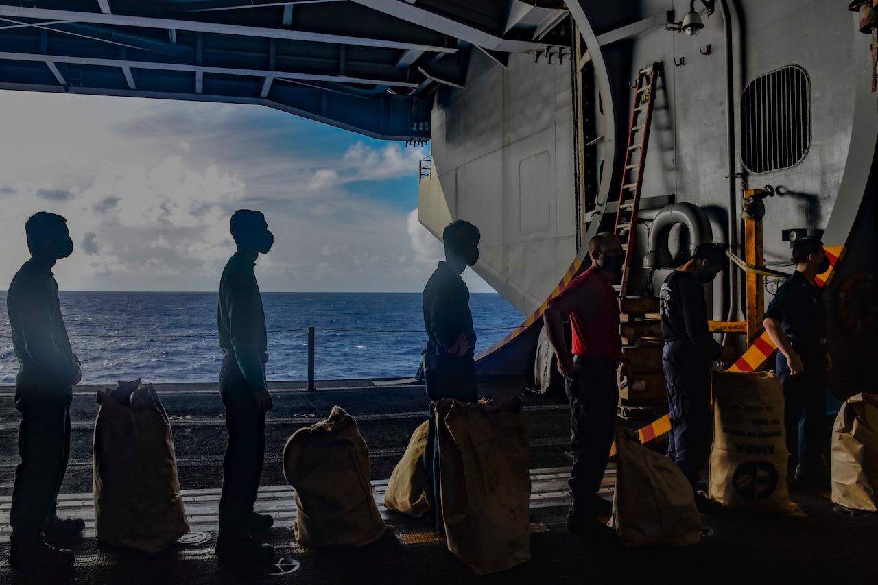 Sailors line up inside a ship. Each has a large bag sitting in front of them.