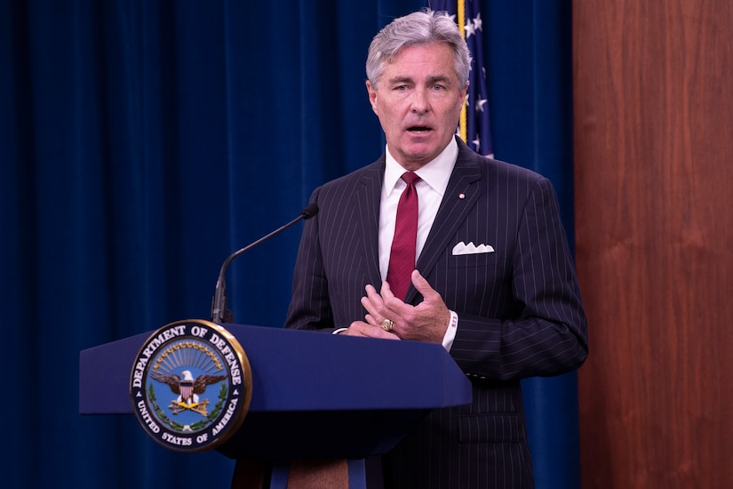 """A man in a business suit stands behind a lectern.  A sign on the lectern says """"Department of Defense -- United States of America."""""""