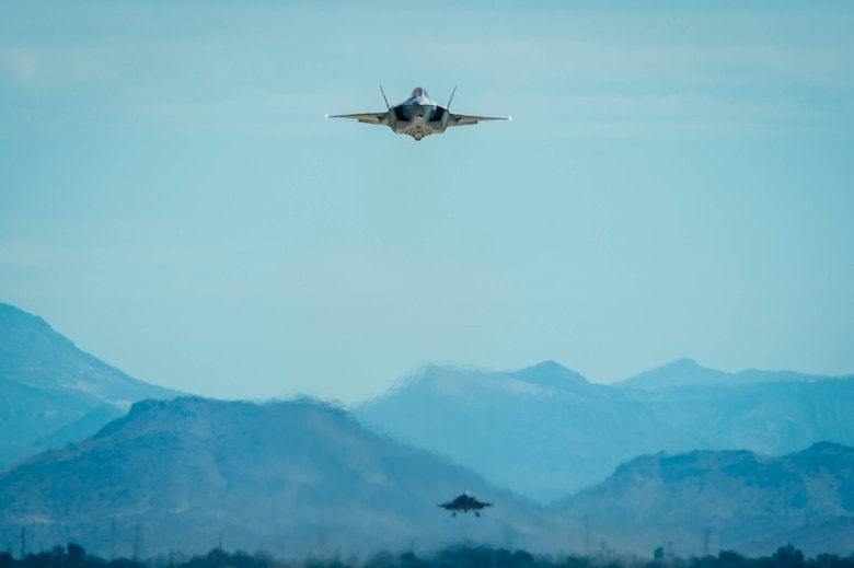 Photo shows two F-35 aircraft taking off with mountains in the background.
