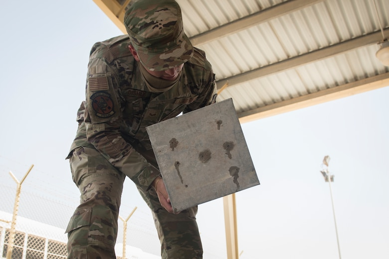 U.S. Air Force Senior Airman Ryan Disher, a vehicle operator assigned to the 379th Expeditionary Logistics Readiness Squadron, removes a drainage pan from a vehicle wash rack at Al Udeid Air Base, Qatar, June 13, 2020.