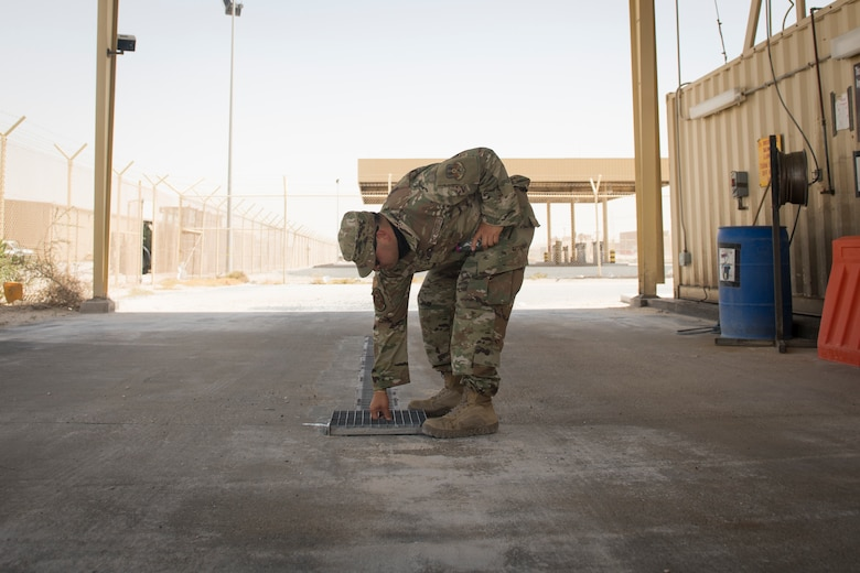 U.S. Air Force Senior Airman Fernando Jimenez, a vehicle operator assigned to the 379th Expeditionary Logistics Readiness Squadron, returns a drainage pan into a vehicle wash rack at Al Udeid Air Base, Qatar, June 13, 2020.
