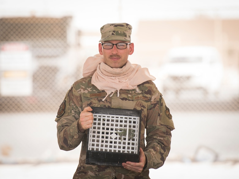 U.S. Air Force Staff Sgt. Justin Grahn, a vehicle operator assigned to the 379th Expeditionary Logistics Readiness Squadron, displays his team's winning submission in the U.S. Air Forces Central Command Spark Tank competition at Al Udeid Air Base, Qatar, June 13, 2020.