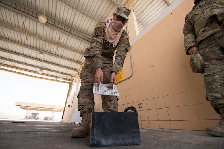 U.S. Air Force Staff Sgt. Justin Grahn, a vehicle operator assigned to the 379th Expeditionary Logistics Readiness Squadron, inspects a prototype drainage pan from a vehicle wash rack at Al Udeid Air Base, Qatar, June 13, 2020.