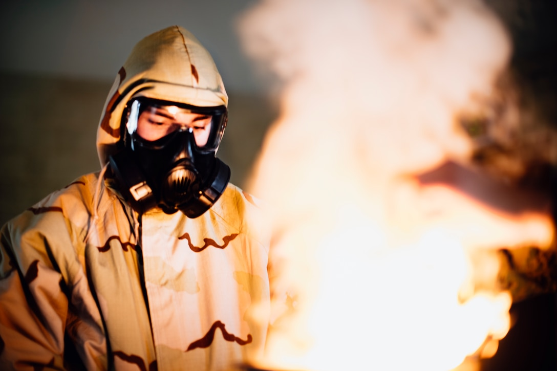 A U.S. Marine burns a non-lethal chlorobenzylidene malononitrile capsule during a gas chamber qualification at Marine Corps Base Camp Pendleton, Calif., June 19.