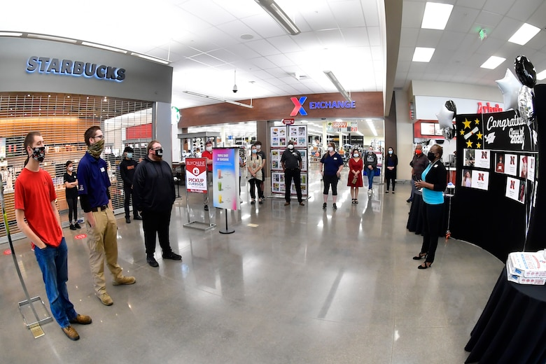 Melony White, AAFES general manager, addresses students, employees, families and friends inside the AAFES Main Exchange at the store entrance.