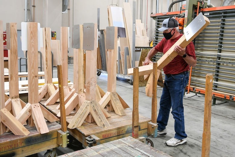 Barry Chase, 309th Maintenance Support Group's wood shop supervisor, loads a stanchion the shop built to hold hand sanitizer dispensers.