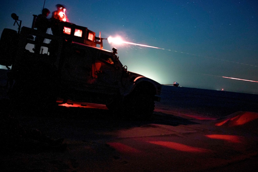 Marines, shown in silhouette and illuminated by red light, stand atop a military vehicle and fire a weapon at night.