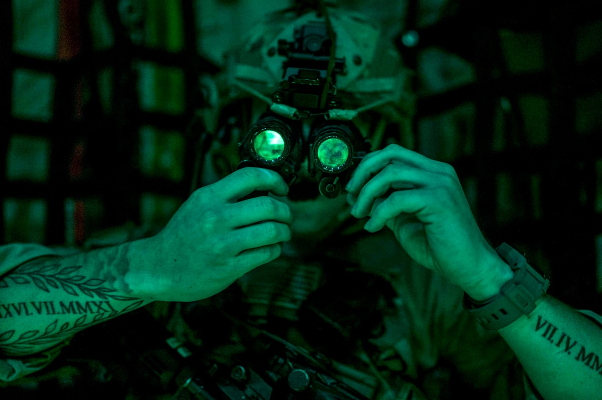 A soldier illuminated by green light adjusts eyewear he's wearing.