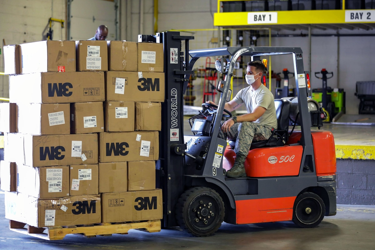 A service member wearing a mask moves boxes with a forklift as a man in the background looks on.with a fork-lift.