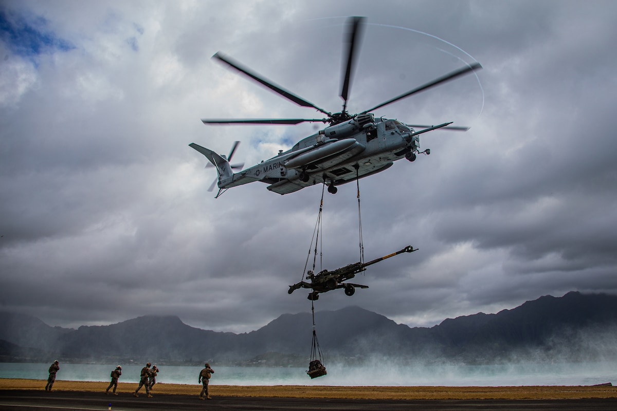 A military helicopter lifts a large weapon.