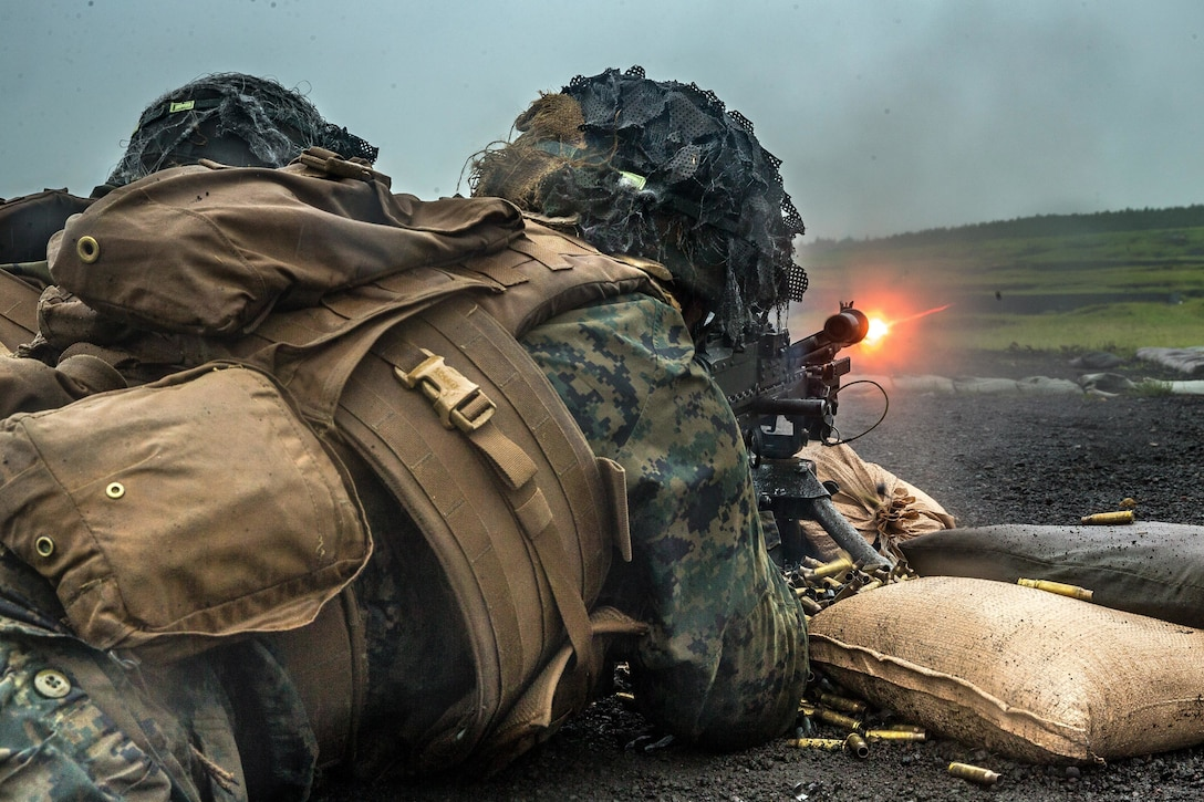 A Marine fires a machine gun while lying on the ground.