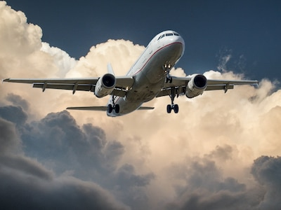 Airplane in air on blue sky and cloud background