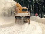 A former military snowblower drives a snowy road.