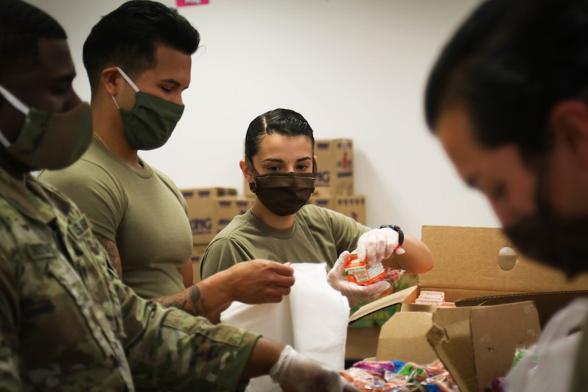 Soldiers wearing face masks assemble packaged meals.