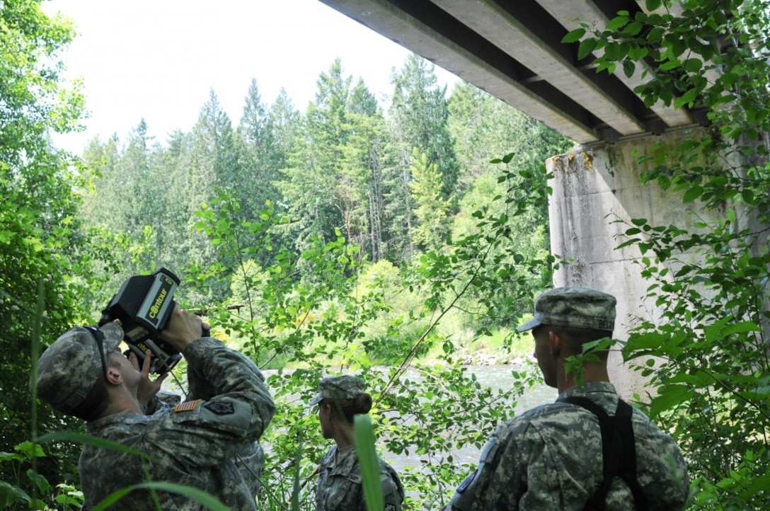 Spc. Christopher Carr (left) and Spc. William Belanger (right) with the 610th Engineer Support Company use a laser range finder to gather and record data on the Nisqually River Bridge while training with the new ENFIRE system June 5. Soldiers with the 14th Eng. Bn., spent a week training on the ENFIRE system which is a digital reconnaissance and surveying equipment instrument set. (US Army photo by Sgt. Austan R. Owen.)
