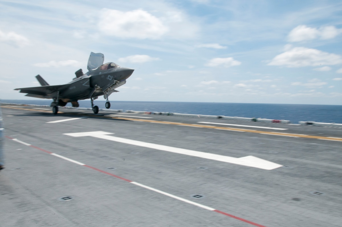 As fast as its name, an F-35B Lightning II screams past a flight deck handler as it takes off during flight operations aboard the amphibious assault ship USS Wasp (LHD 1)