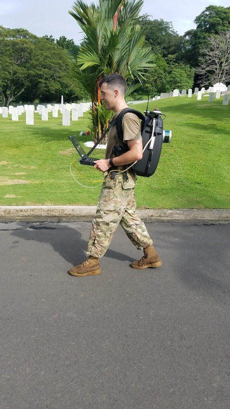 Spc. Zachary Wright, an Engineer Soldier with the 512th Engineer Detachment walks along a road in Corozal American Cemetery in Panama City, Panama, June 28, 2018, with a Light Detection and Ranging (LiDAR) system, which works by sending out a beam of light and measuring the time it takes to return to the sensor. Wright is working as part of a certifying program to ensure precision and accuracy at the final resting places of American service members. The pilot program is supported through a cooperative effort between the American Battle Monuments Commission, Arlington National Cemetery, the United States Army Corps of Engineers, the Army GeoSpatial Center and Product Director Combat Terrain Information Systems. (U.S. Army Photo/Courtesy USACE)