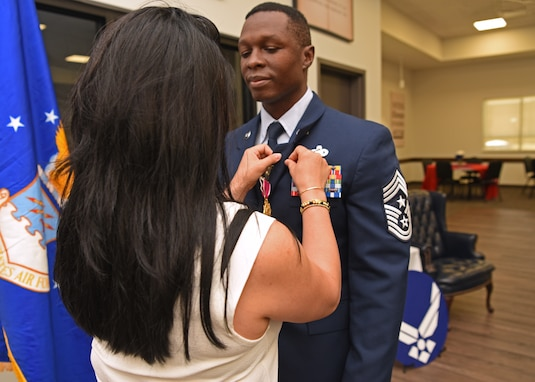 Spouse Michelle Kirkpatrick pins a retirement emblem on the uniform of U.S. Air Force Chief Master Sgt. Lavor Kirkpatrick, during his retirement ceremony at the Cressman dining facility on Goodfellow Air Force Base, Texas, June 19, 2020. Kirkpatrick was the command chief of the 17th Training Wing and retired after serving a total of 23 years to his country. (U.S. Air Force photo by Airman 1st Class Abbey Rieves)