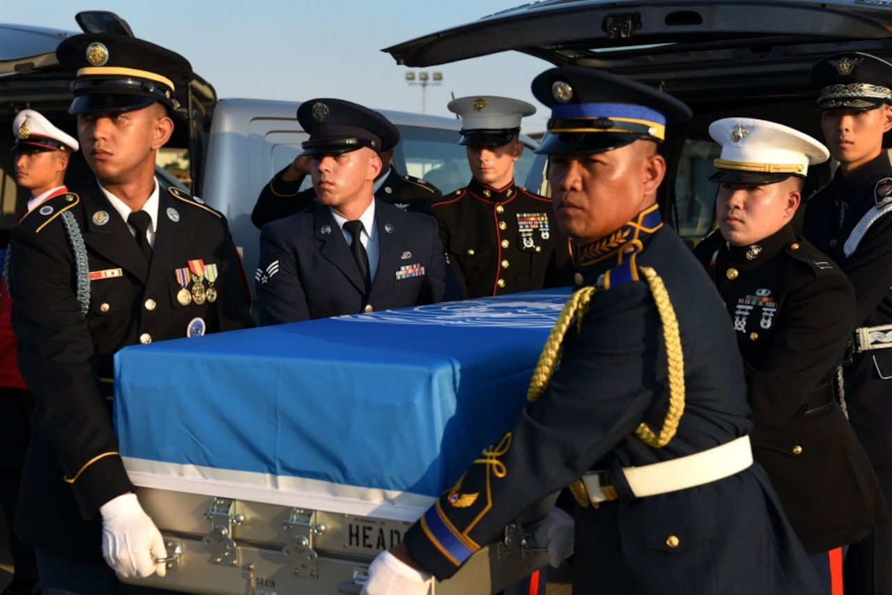Service members carry a metal box that is draped with a United Nations flag.