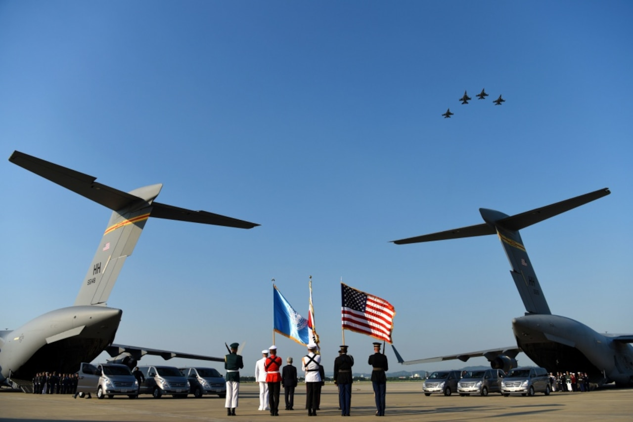 An honor guard stands by boxes of remains draped with United Nations flags on a military cargo plane.