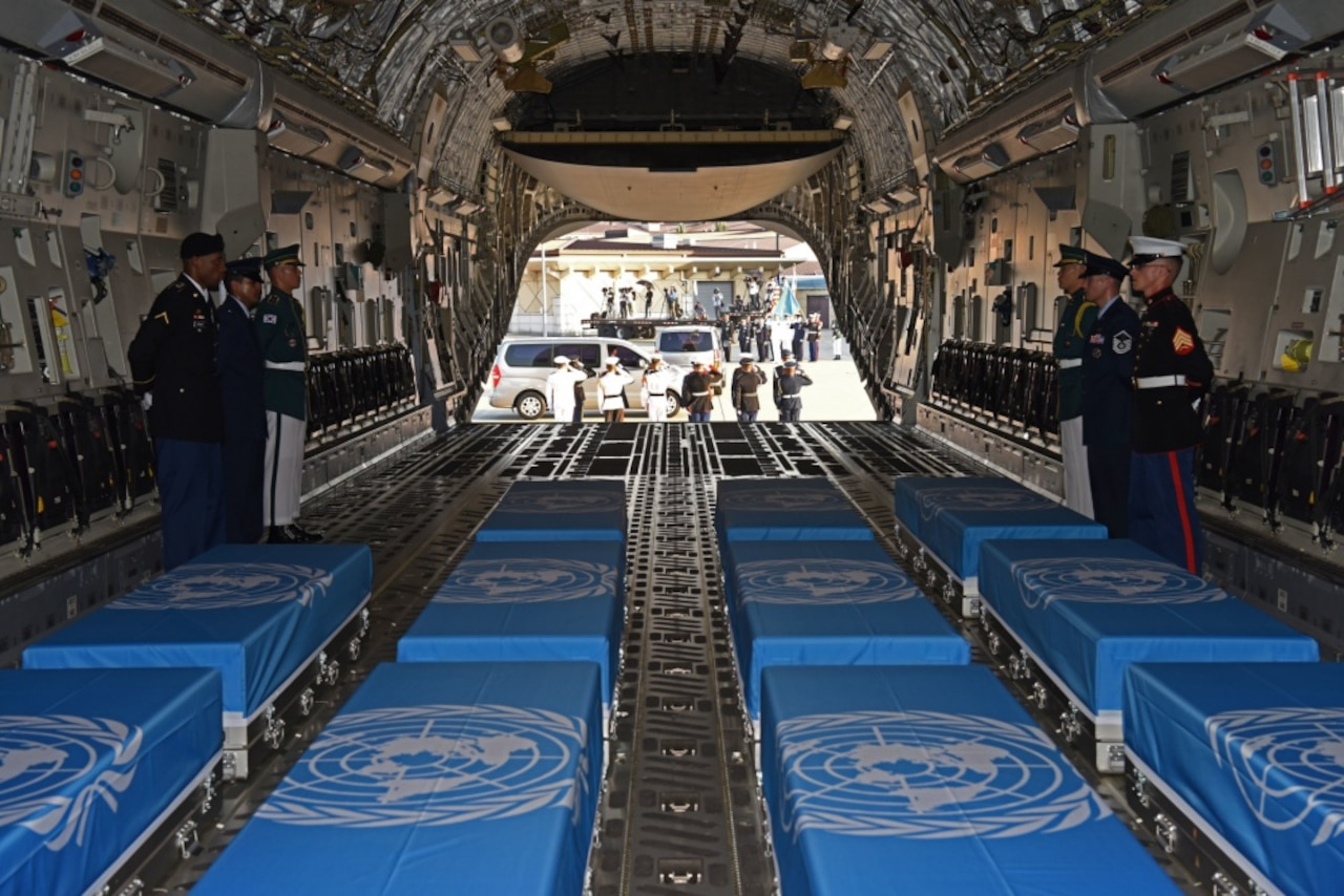 An honor guard stands by boxes of remains draped with United Nations flags on a military aircraft.