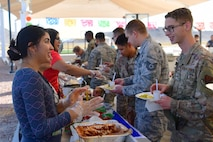 Airmen in uniform and civilian entire try a culturally diverse spread of food that is lined up buffet style.