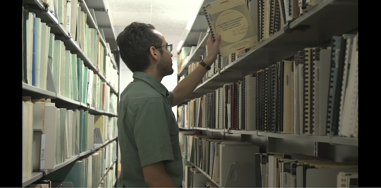 An Edwards Air Force Base engineer consults a Technical Report in the 812th Test Support Squadron archives. The Scientific and Technical Information Program Distribution Statements identify who may view the contents of a report and are prominently displayed on the front cover. (Courtesy photo)